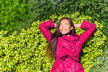 Happy spring pink fashion trench coat woman relaxing lying on green plants wall. Asian smiling girl lying down enjoying freedom carefree dreaming stress-free.