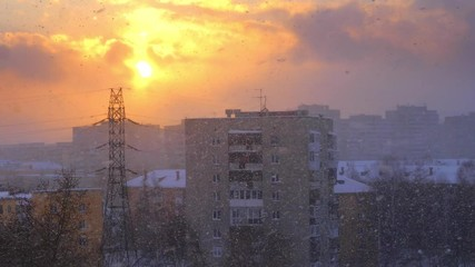 Fotobehang - Snowfall snow falling snowstorm in winter city during epic sunset. Slow motion, 4K UHD.