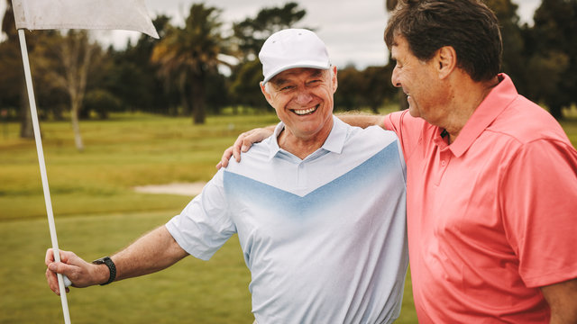 Two smiling senior golf players on the green