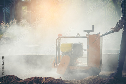 Construction worker using a concrete saw, cutting stones in