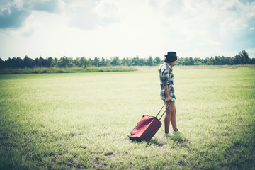 Beautiful girl in a meadow with a red bag.