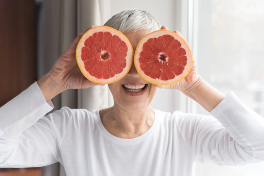 Woman holding grapefruit on her eyes