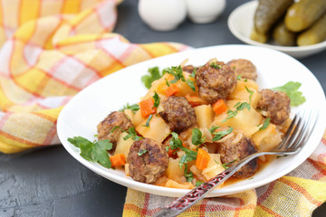 Stewed potatoes with meatballs on a white plate