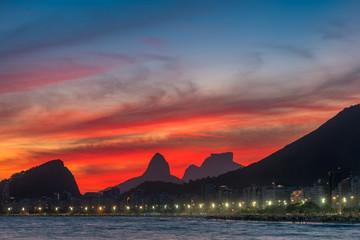 Wall Mural - Night View of Copacabana Beach With Beautiful Red Sky Just After the Sunset, and Mountains in the Horizon, in Rio de Janeiro, Brazil