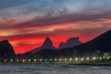 Fototapete - Night View of Copacabana Beach With Beautiful Red Sky Just After the Sunset, and Mountains in the Horizon, in Rio de Janeiro, Brazil