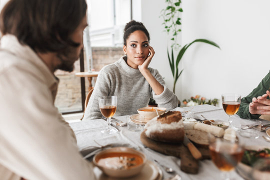 Young beautiful african american woman with dark curly hair sitting at the table leaning on hand thoughtfully looking at friend while spending time in cozy cafe