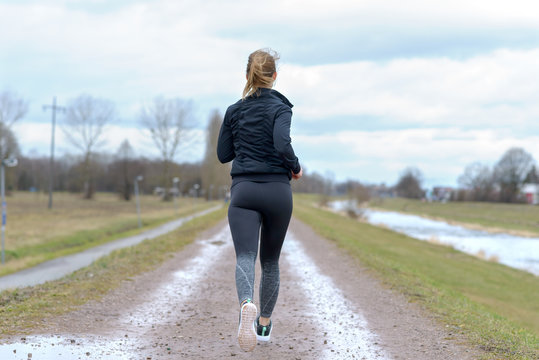 Fit muscular woman jogging away from camera