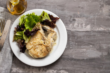 boiled fish with sauce and green salad on white plate
