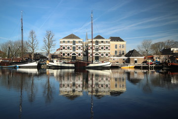 old museum harbor of Gouda with historic ships at mallegatsluis sluice to the Hollandsche IJssel in the Netherlands