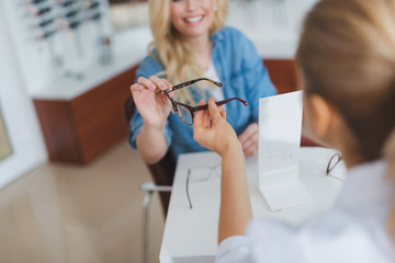 Professional female optician passing glasses to her patient