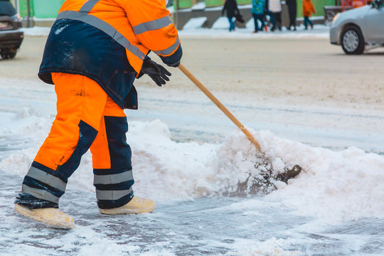 Communal services worker sweeps snow from road in winter, Cleaning city streets and roads after snow storm. Moscow, Russia.