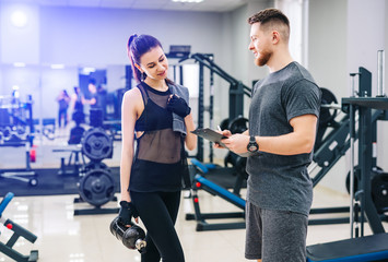 Personal trainer and his female client standing together and discussing nutrition or training plan on clipboard. Healthy lifestyle, fitness concept