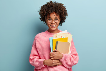 Education and ethnicity concept. Optimistic glad dark skinned young woman with pleased expression, holds textbooks nad papers, rejoices learning new information, isolated over blue background