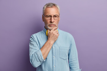 Headshot of attractive wrinkled man with grey hair holds chin, contemplates about life, dressed in stylish shirt, wears spectacles, poses over purple background. People, age, experience concept