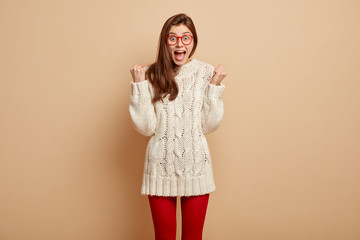 Successful female winner clenches fists with triumph, wears long white sweater and red tights, feels overemotive, isolated over beige background, smiles joyfully. People, victory, celebration concept