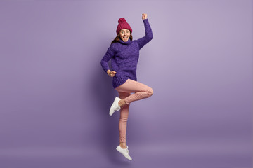 Bright image of optimistic woman feels energetic and elated, raises hands and legs, has fun indoor, wears warm clothes, isolated over purple background, rejoices good life. Optimism concept.