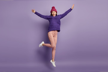 Cheering joyful young woman spreads hands, jumps high, photographed in motion, wears knitted hat with pompon, sweater, white sneakers, isolated over purple background. Positive feelings concept