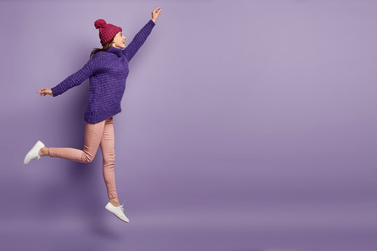 Buoyant pleased woman jumps in air, spreads hands and legs, wears knitted hat, purple sweater, trousers and sneakers, celebrates something with happiness. Mock up free space over violet wall