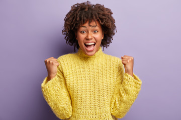 Overjoyed carefree African American woman raises clenched fists, shows success gesture, triumphs over purple background, wears knitted winter yellow sweater, isolated over purple background.