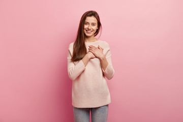 Impressed friendly pleasant looking woman keeps hands on chest, touched by compliment, smiles positively, wears jumper and jeans, models over pink background, looks at camera with great pleasure