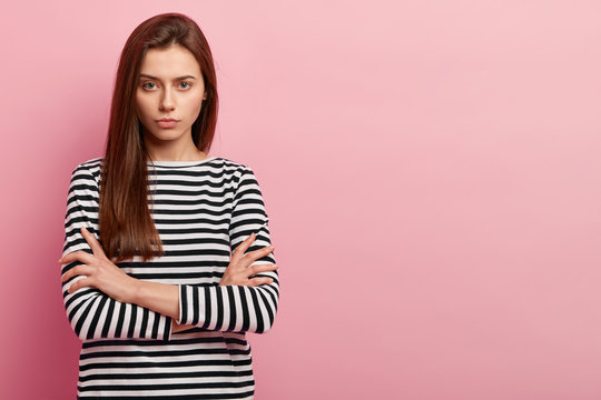 Photo of attractive sad young European woman keeps arms folded, has brown long hair, dressed in striped casual jumper, poses over pink background with free space for your advertisement or promotion