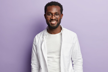 Photo of attractive black man with thick bristle, toothy smile, wears white stylish shirt, round spectalces, rejoices new task for accomplishment, isolated over purple background. Ethnicity concept