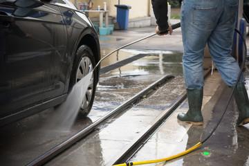 Man Using Water Pressure Machine to Wash a Car on Blurred Background