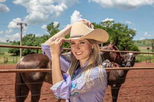 Beautiful blonde cowgirl with hat standing near the horse ranch background