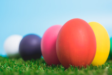 Blue Easter eggs clean on grass and pink background