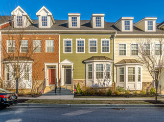Typical American town house, town home neighborhood with colorful real estate houses at a new construction East Coast Maryland location with blue sky