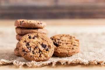 Chocolate chip cookies on sackcloth on wood table.  Copy space for your text or image.