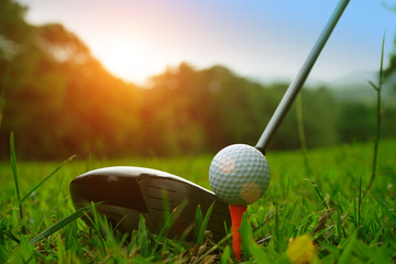 golf club and golf ball close up in grass field with sunset. Golf ball on tee in golf coures at Thailand