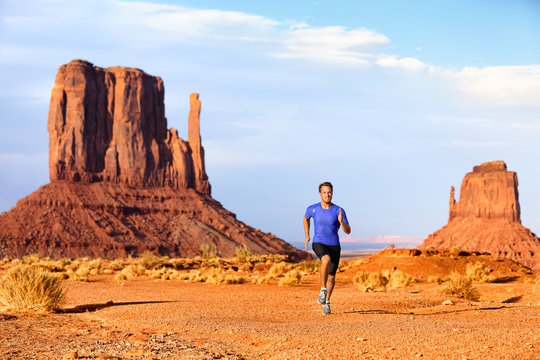 Trail running runner athlete doing race goal challenge. Fitness man sprinting across desert in Monument Valley, cross country marathon endurance training in Arizona, Utah, USA. American travel.