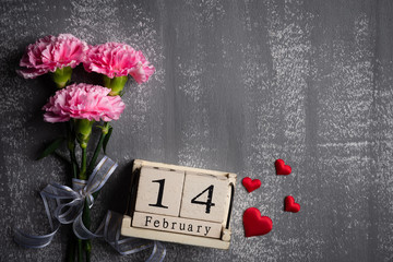 Valentines day and love concept. Pink carnation flower with February 14 text on wooden block calendar and red heart and on gray wooden background.