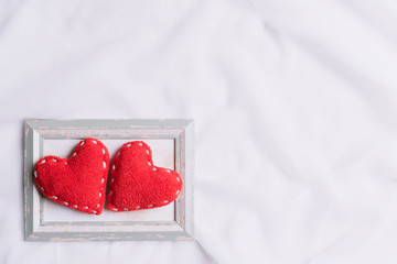 Valentines Day and symbol of love. Two red hearts in picture frame on white fabric background.