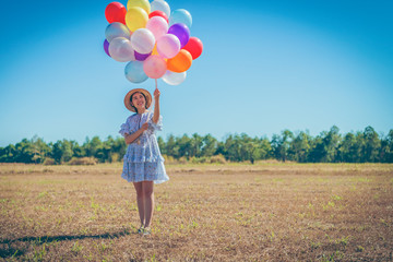 Young couple at the meadow with balloons
