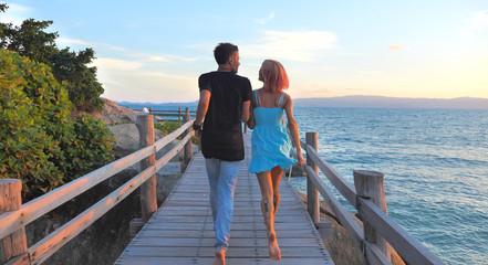 Beautiful Young Couple in Love spend time Together at Sunset time with Sea view