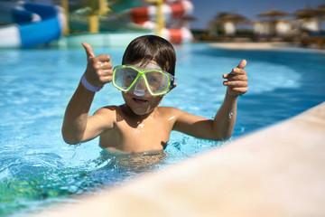 Small boy posing in green swim mask in aquapark