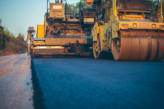 Road works in the city. Working on special equipment cut off the old asphalt on a Sunny summer day