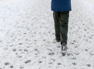 Legs of a man walking along a snowy road