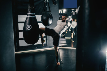 Muscular powerful Caucasian kick-boxer with boxing gloves on and in sportswear kicking bag in dark gym.