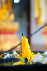 yellow candle,used candlewick and melted candle in Buddhist temple