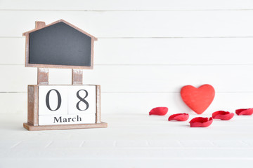 Womens day concept, happy womens day, international womens day. March 8 text wooden block calendar with red heart and red roses petal on white wooden background.