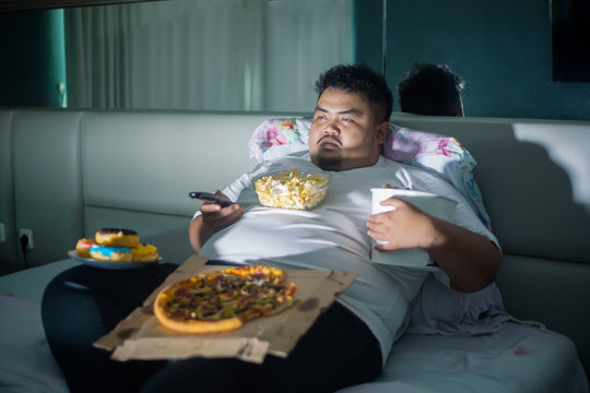 Asian obese man eating junk foods before sleep
