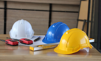 yellow, blue and white hard safety helmet for safety project of workman as engineer on table wooden.