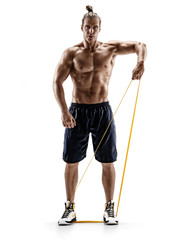 Man with athletic body performs exercises using a resistance band. Photo of muscular man isolated on white background. Strength and motivation. Full length