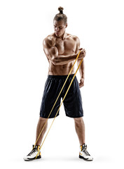 Young strong man with naked torso performs exercises using resistance band. Photo of muscular man isolated on white background. Strength and motivation. Full length