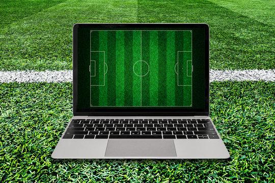 Laptop on soccer grass field background.