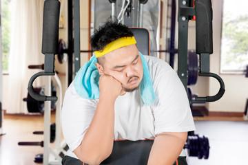 Obese man sleeping on the exercise machine