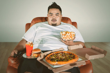 Obese man watching TV with junk foods at home
